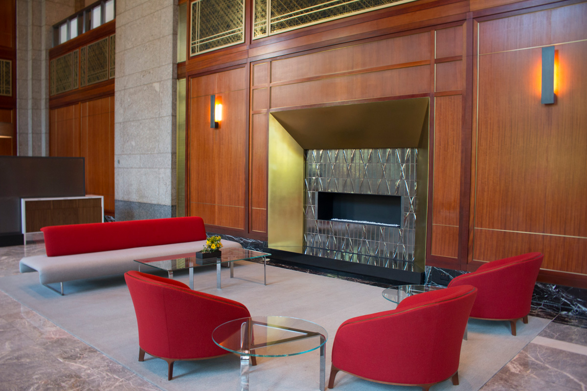Atrium fireplace with acoustical brass panels and casework