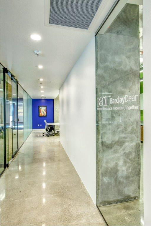 Open Square hallway with exposed concrete and glass windows