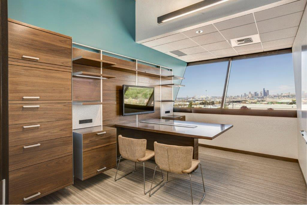 Open Square office with wood desk and cabinets, and Seattle view